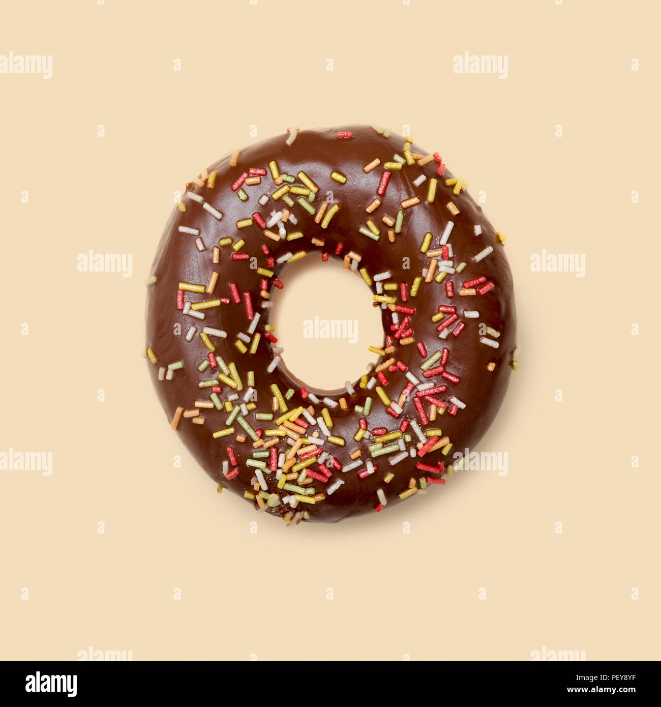 Chocolate doughnut with sugar strands, studio shot. - Stock Image