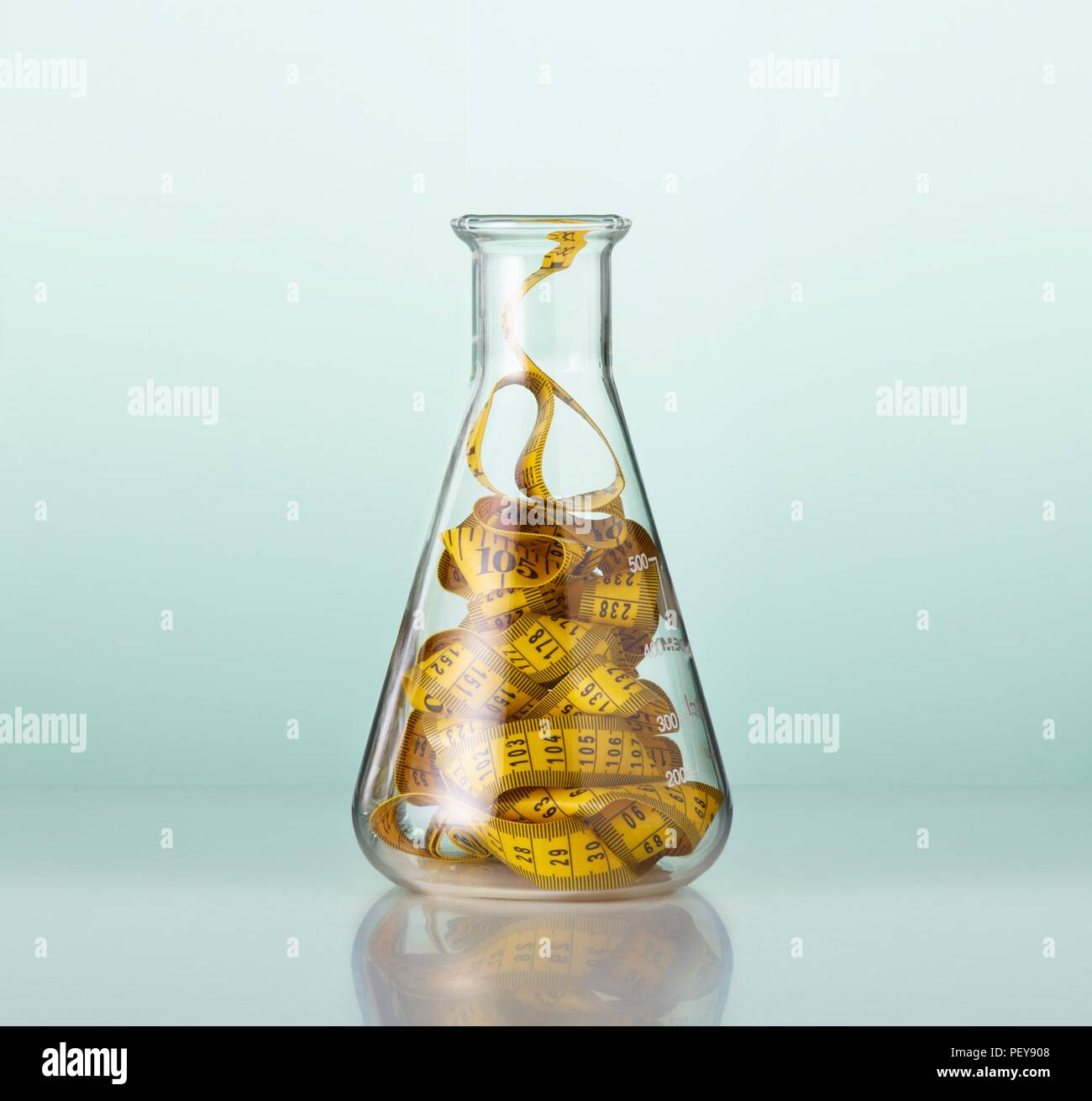 Laboratory glassware with tape measures. - Stock Image