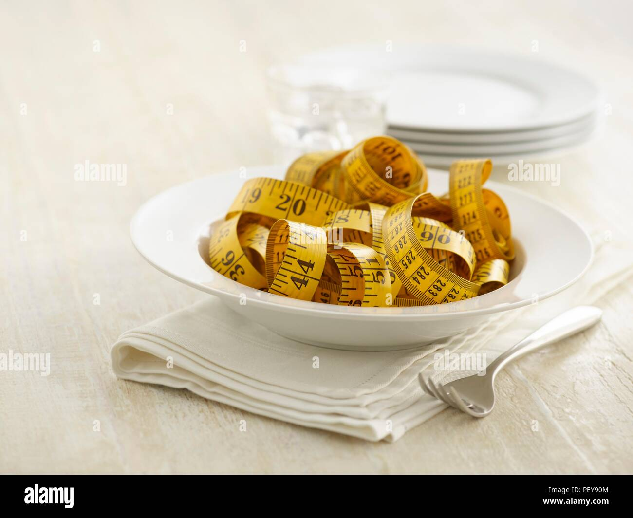 Pasta bowl with tape measure. - Stock Image