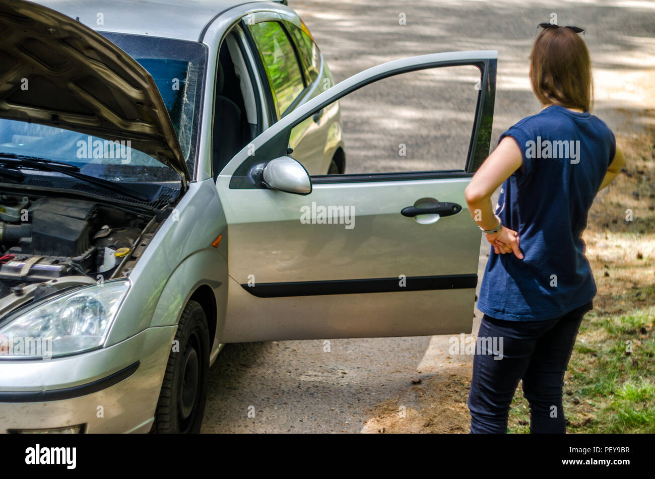 Girl driver near the open hood of a broken car. Broken car on the roadside with an open hood, trunk and doors. - Stock Image