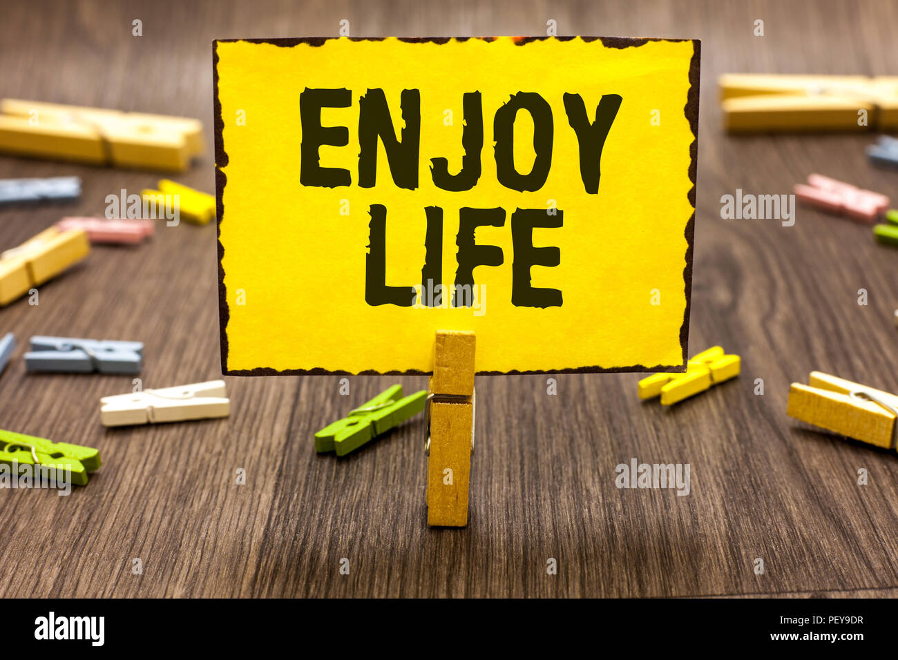 Text sign showing Enjoy Life. Conceptual photo Any thing, place,food or person, that makes you relax and happy Clothespin holding yellow paper note se - Stock Image
