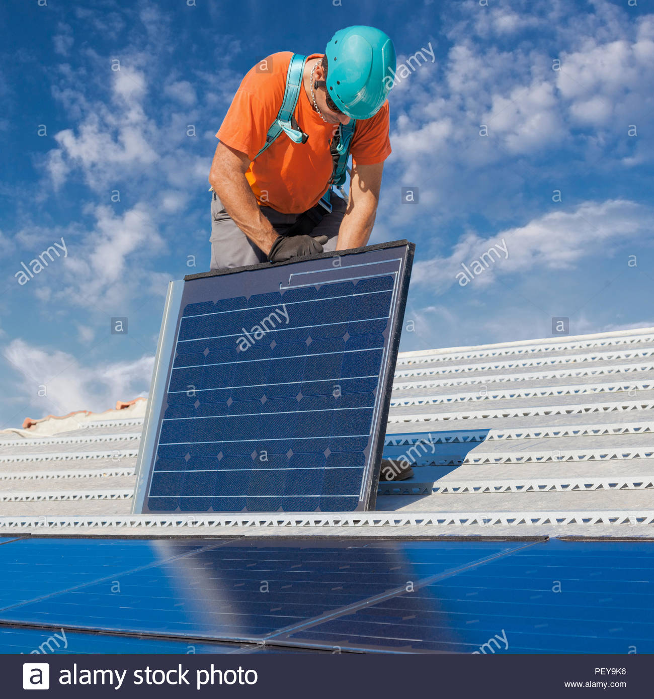 Man Solar Panel Stock Photos Images Alamy With Corrugated Thin Film Cells On Wiring Panels In At Work Installing Alternative Energy Photovoltaic Roof Image
