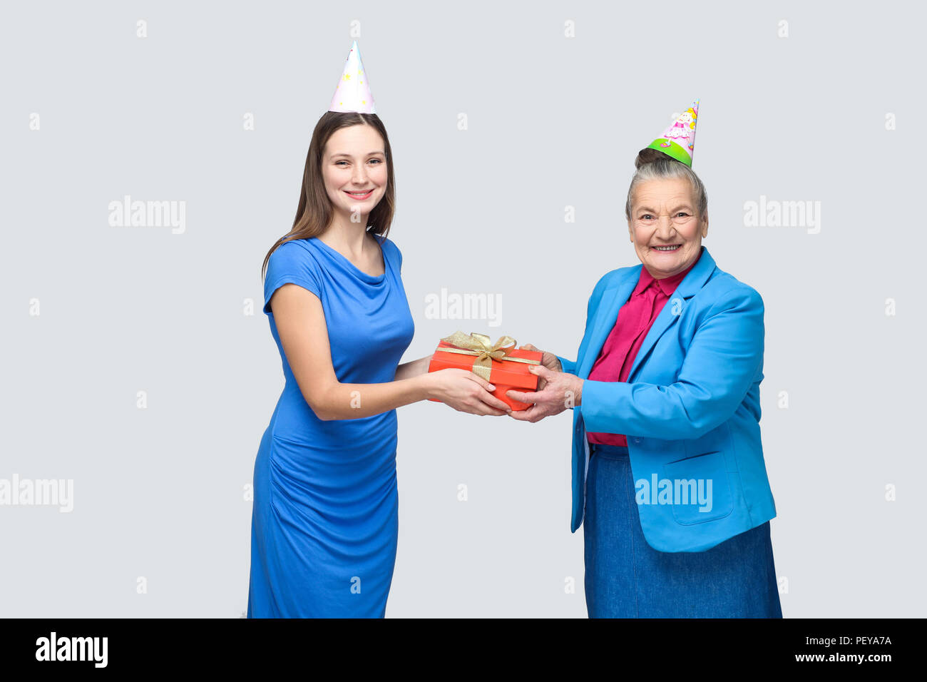 Grandmother In Blue Suit And Hat Holding Red Gift Box Giving To Her Lovely Granddaughter On Birthday Family Happiness Life Event Celebration
