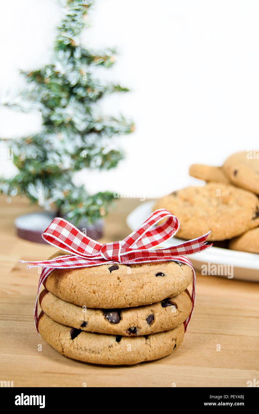 chocolate chip cookies tied with red and white gingham ribbon and bow with Christmas tree Stock Photo
