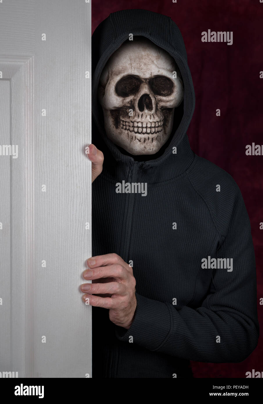 Halloween theme of stalker with skull mask entering a home - Stock Image