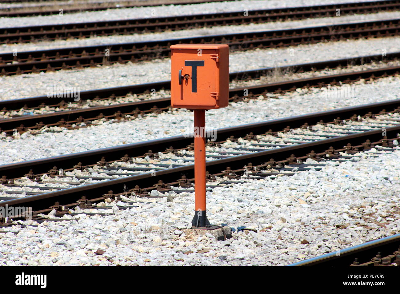 Railway trackside orange communication utility box with lock and key mounted on metal pole and positioned on gravel between railway tracks on warm sun Stock Photo