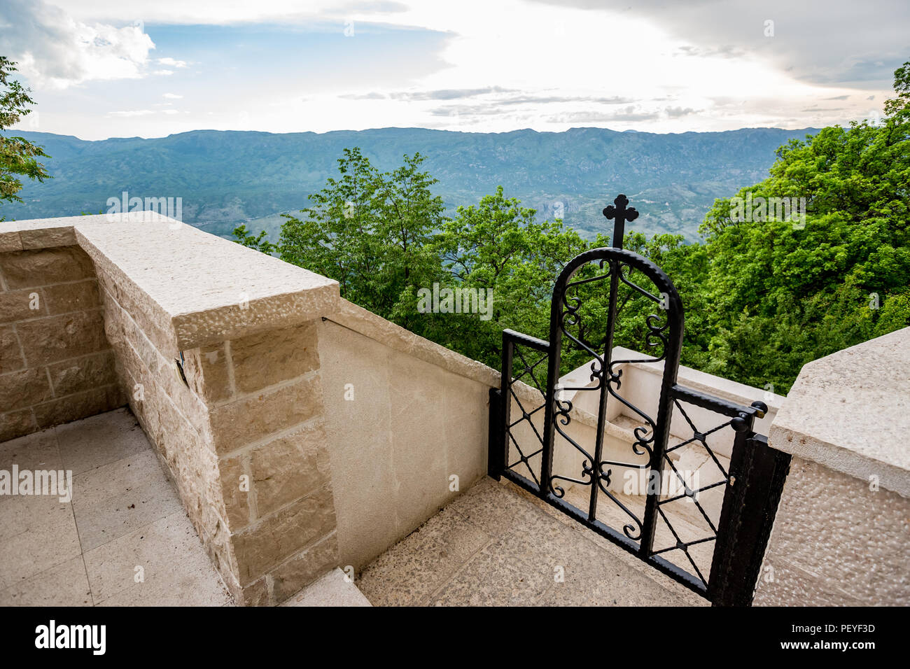 Black painted metallic arc door with decorations and cross on top and beautiful scenery view towards mountains in Montenegro - Stock Image