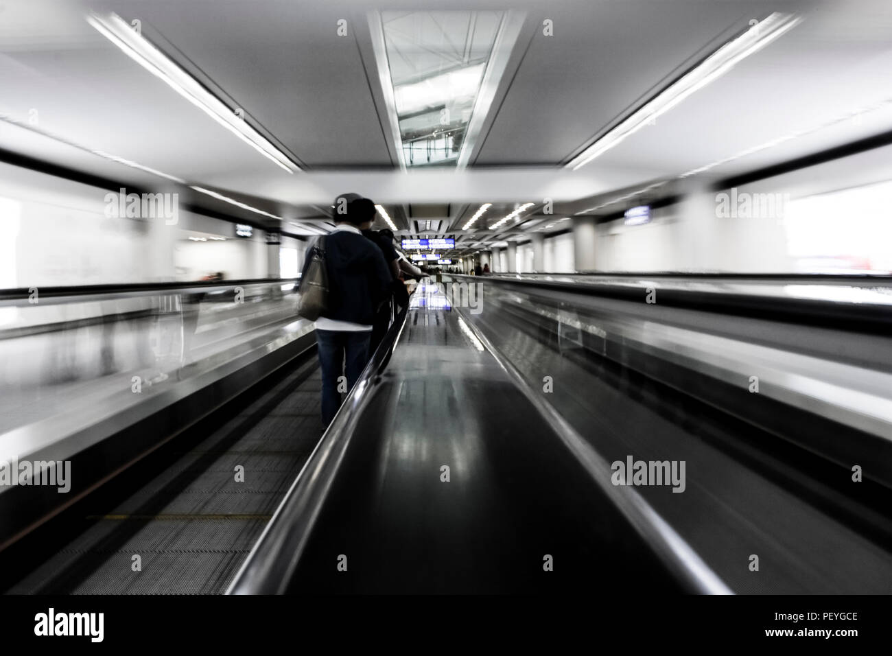 Traveling through airport on escalator symbol for fast pace speed of time jet lag and rush - Stock Image
