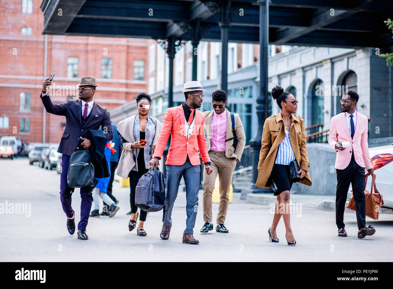 atractive guy is recording the video while his colleagues are in haste to the train station - Stock Image