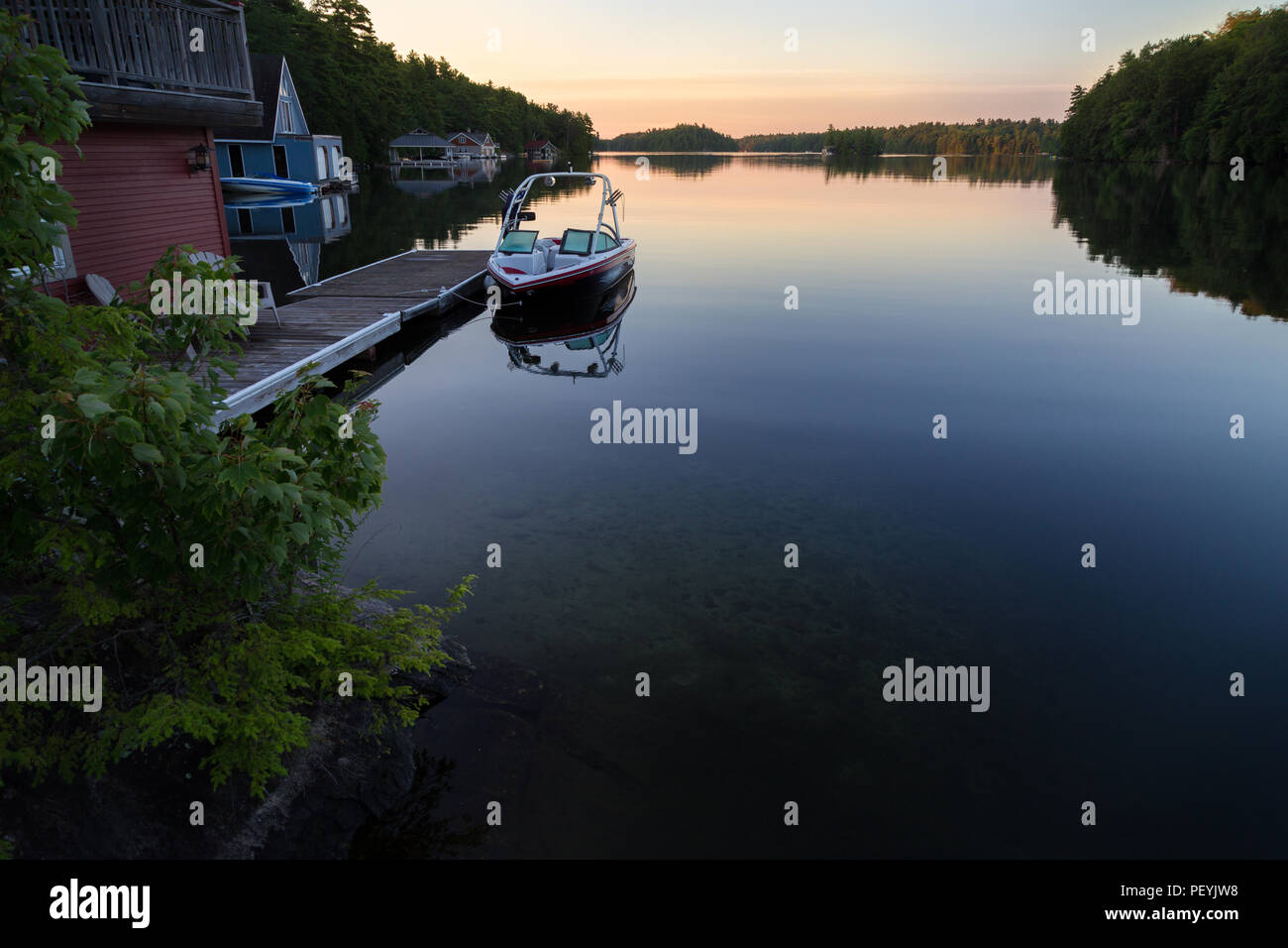 A boathouse with a wakeboard boat parked at it on Lake Joseph at dawn. - Stock Image