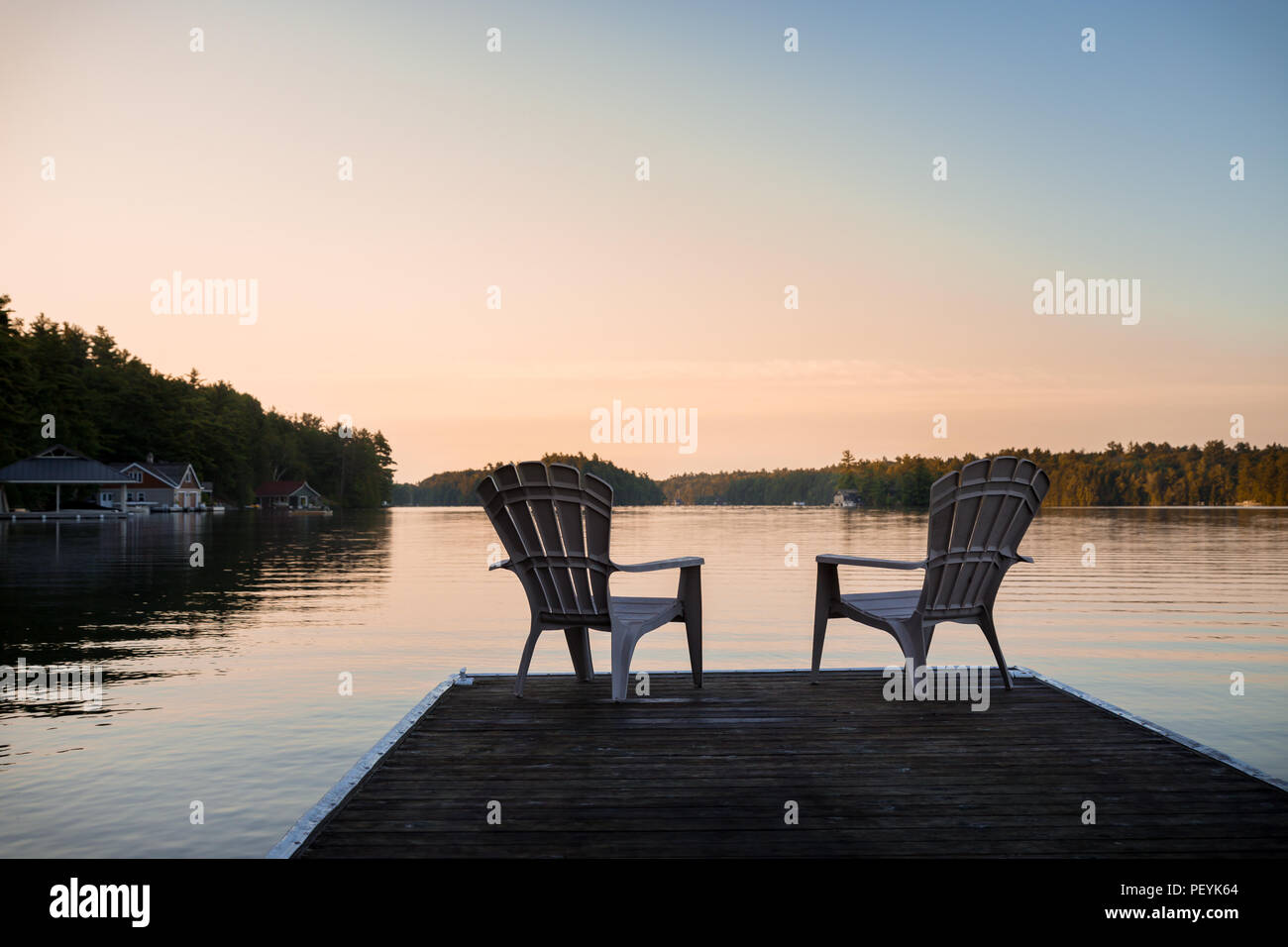 Muskoka chairs sitting at the end of a dock in front of Lake Joseph at sunrise. - Stock Image