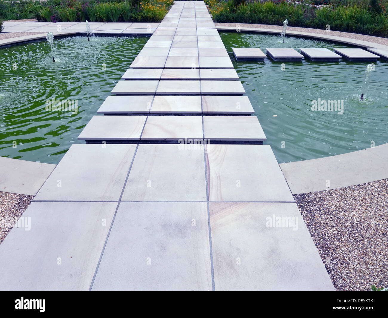 Sharp clean cut stone slabs and various formal pathways & decorative pond area in a large private country house garden in England Property released - Stock Image