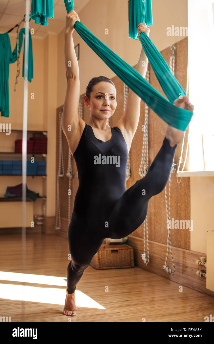 young,positive,beautiful woman is doing stretching splits with hammock in the modern gym. development of flexibility Stock Photo