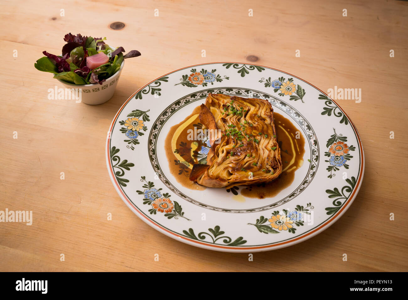 A plate of timballo pasta with a side salad. - Stock Image