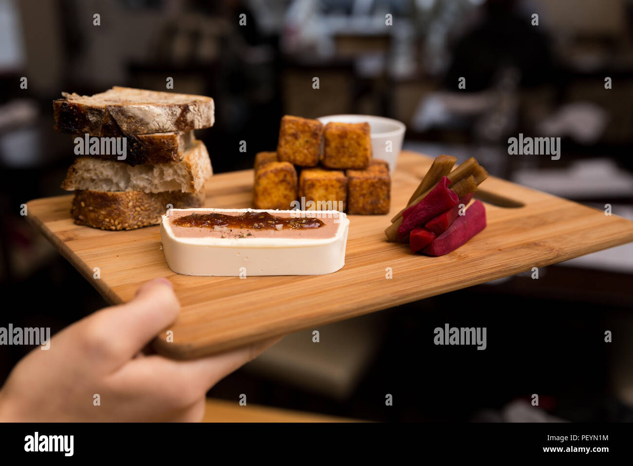 A European style appetizer platter consisting of chicken liver mousse, polenta fritters, bread, and pickled carrots. - Stock Image