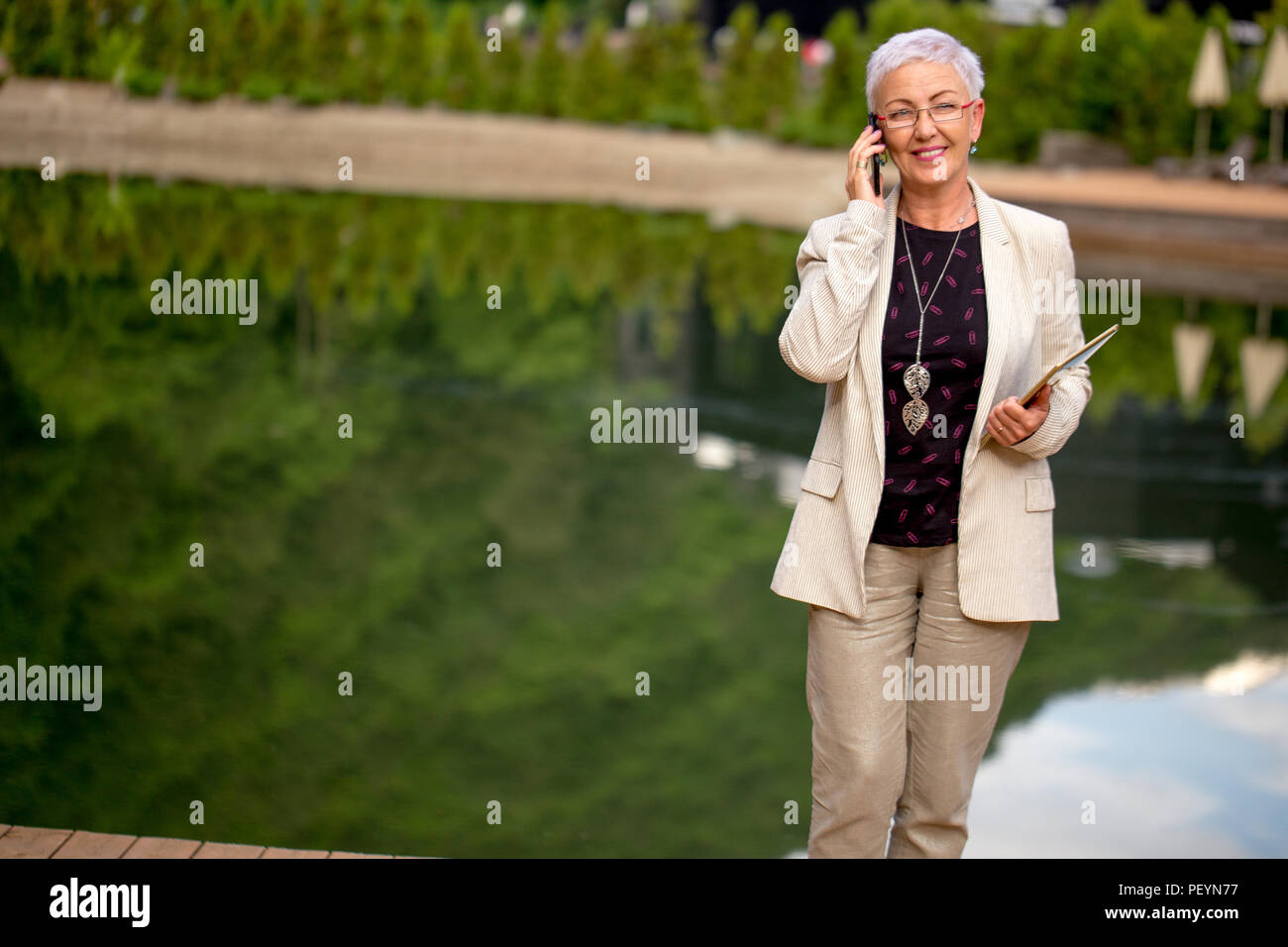 a mature tour guide is taking with holidaymakers on the phone outdoors.permissive temporary duty - Stock Image