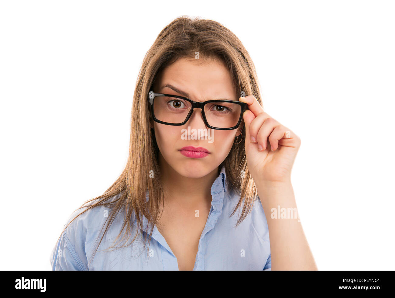 Young modern woman looking puzzled while touching eyeglasses in doubts isolated on white background - Stock Image