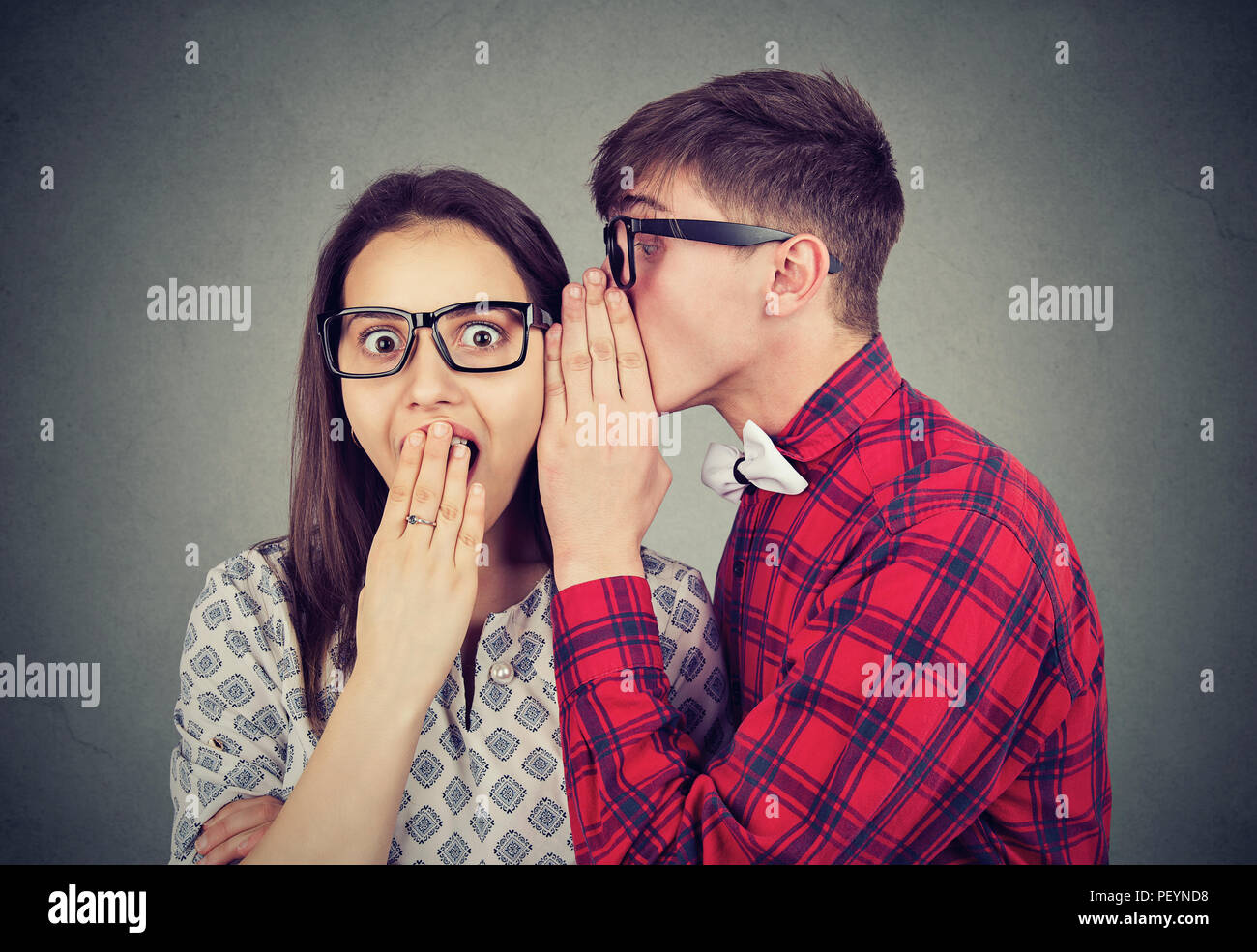 Young man in glasses telling secret to woman looking shocked while standing on gray background - Stock Image