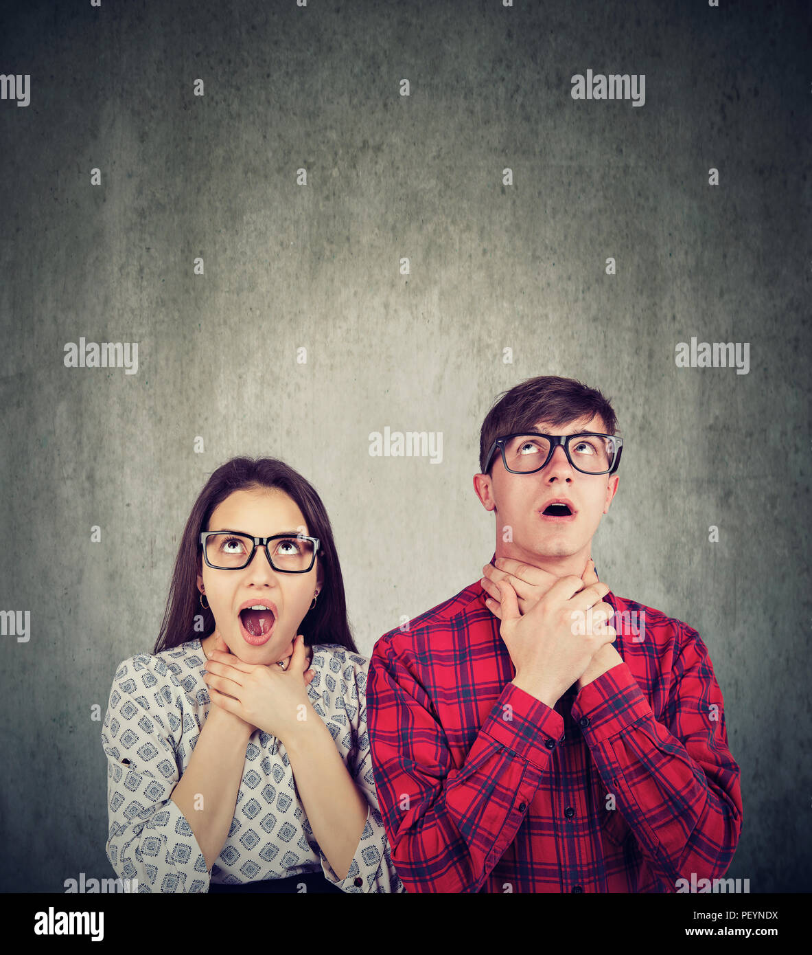 Young man and woman suffocating themselves looking irritated with being in relationship and looking up - Stock Image