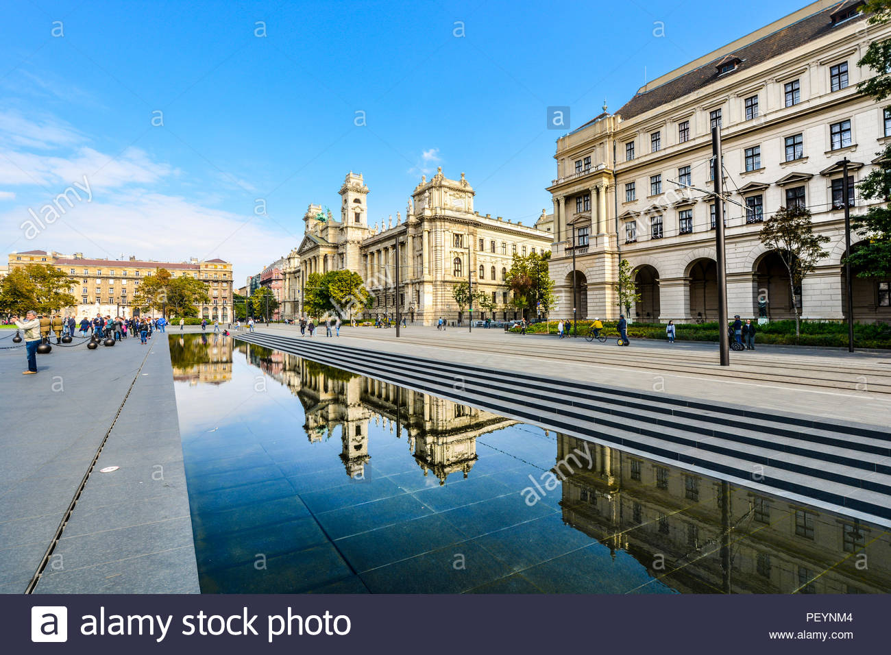 Tourists watch Hungarian guards in Parliament Square as Hungarian government buildings reflect in the large reflecting pool in Budapest, Hungary - Stock Image