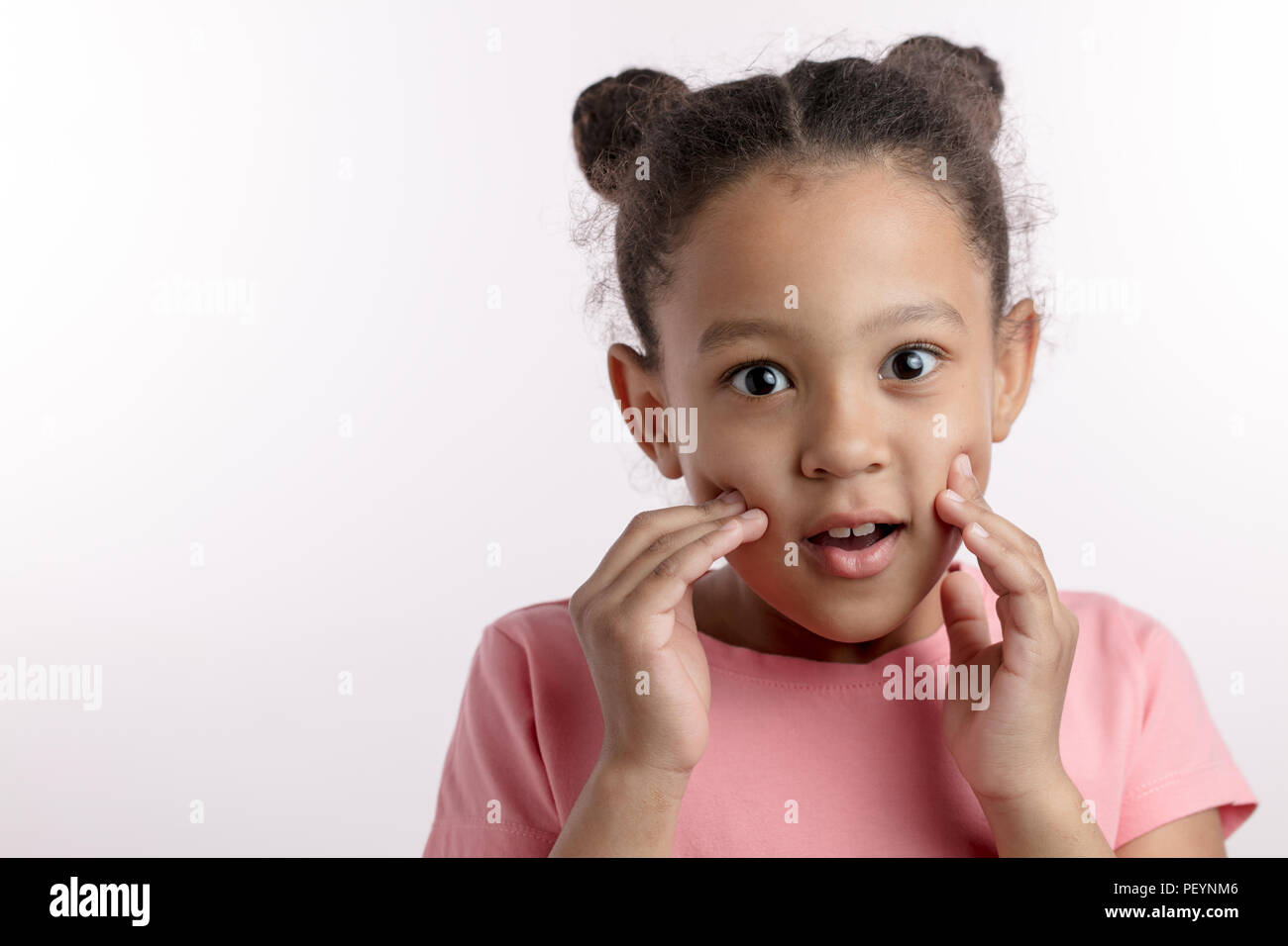 surprised little dark-haired girl with new hairstyle. amazemen concept. cheerful emotional mulatto kid with fingers on her cheeks. copy space. isolate - Stock Image