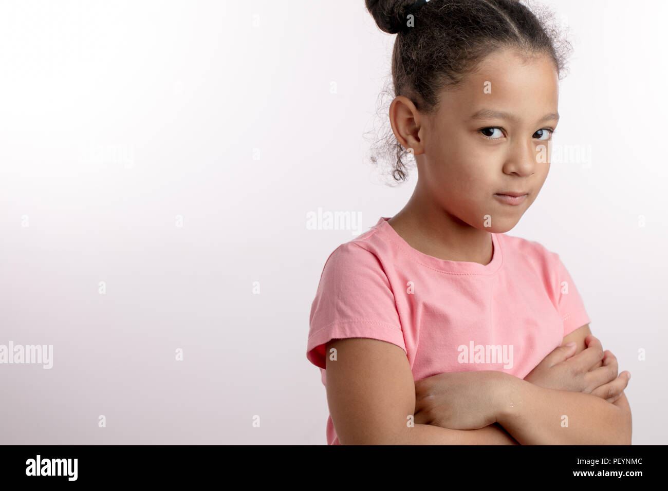 upset beautiful girl standing with crossed arms. black-haired kid is resenting parents. awesome unhappy girl taking offence. bad mood.child showing he - Stock Image