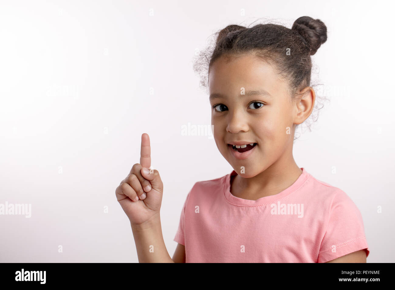 clever girl raising her finger up.posotive kid is pointing at the copy space.direction concept - Stock Image