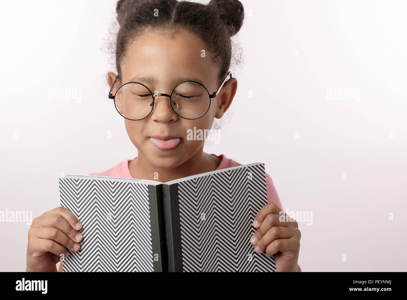 naughty girl doesn't like to read books. nice girl in glasses with closed eyes is holding a notepad. copy space. dark-haired child teasing somebody - Stock Image