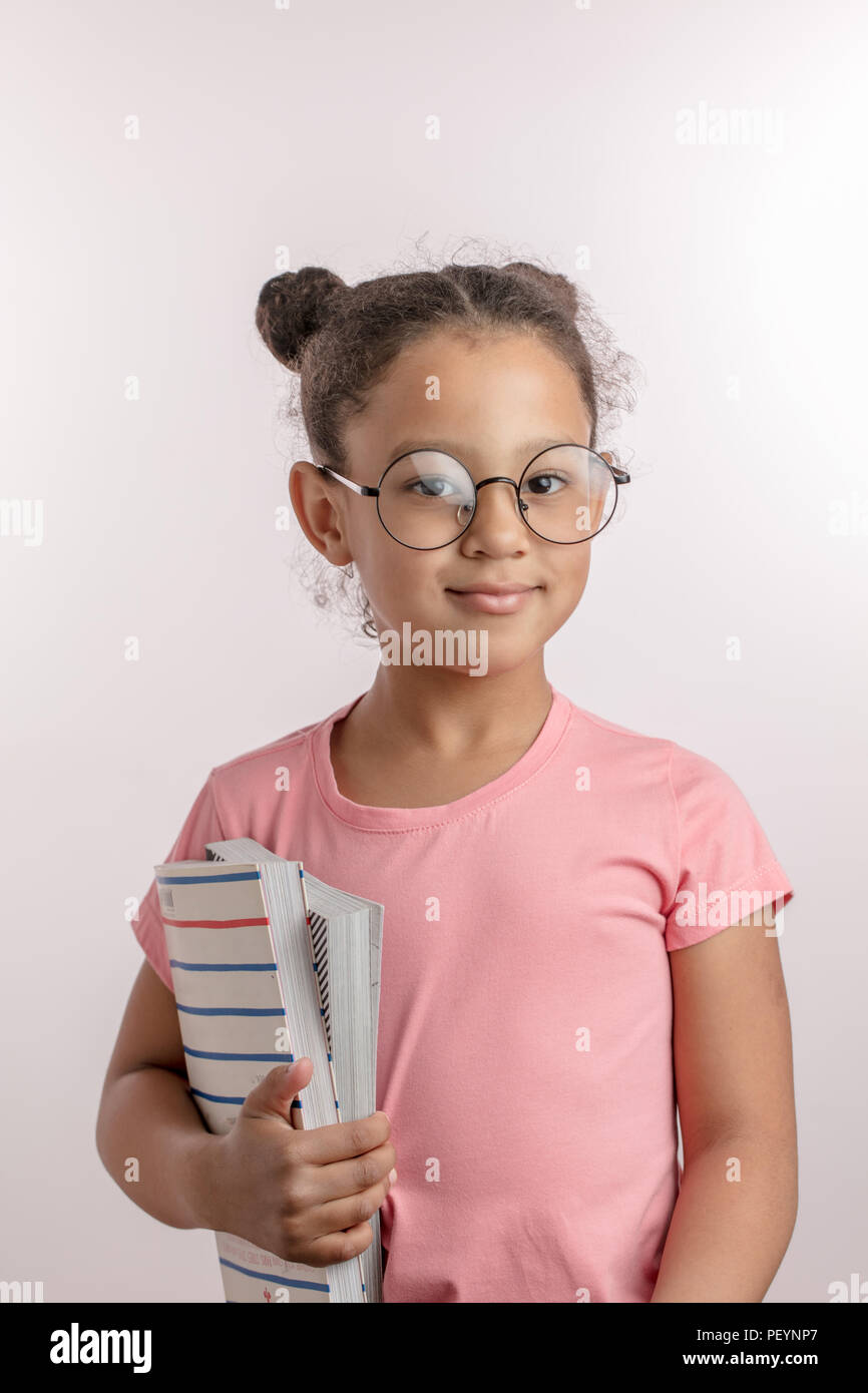 awesome girl is going to school. pleasant child with hairbun is going to do homework. learning concept - Stock Image