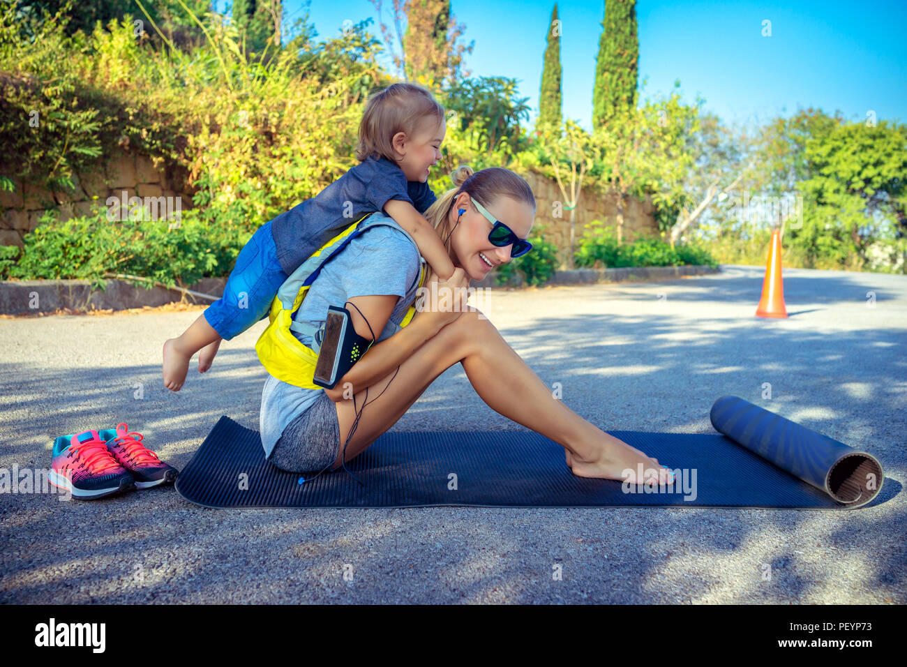 Sportive mother with child outdoors doing fitness excercise,  happy family together on workout, active healthy lifestyle - Stock Image