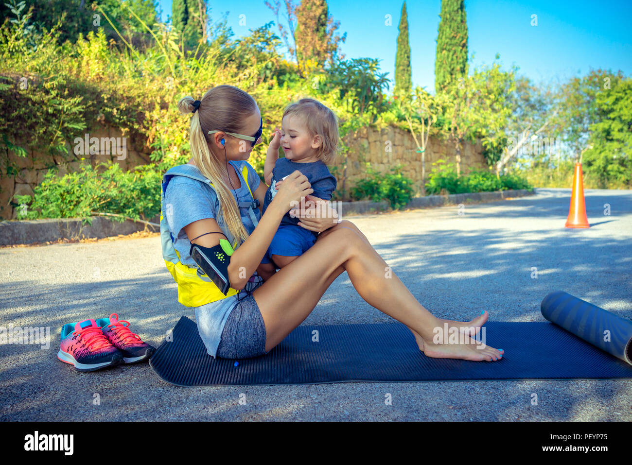 Mother with baby doing exercise outdoors in the park in bright sunny day, happy family together playing sports, healthy active life - Stock Image