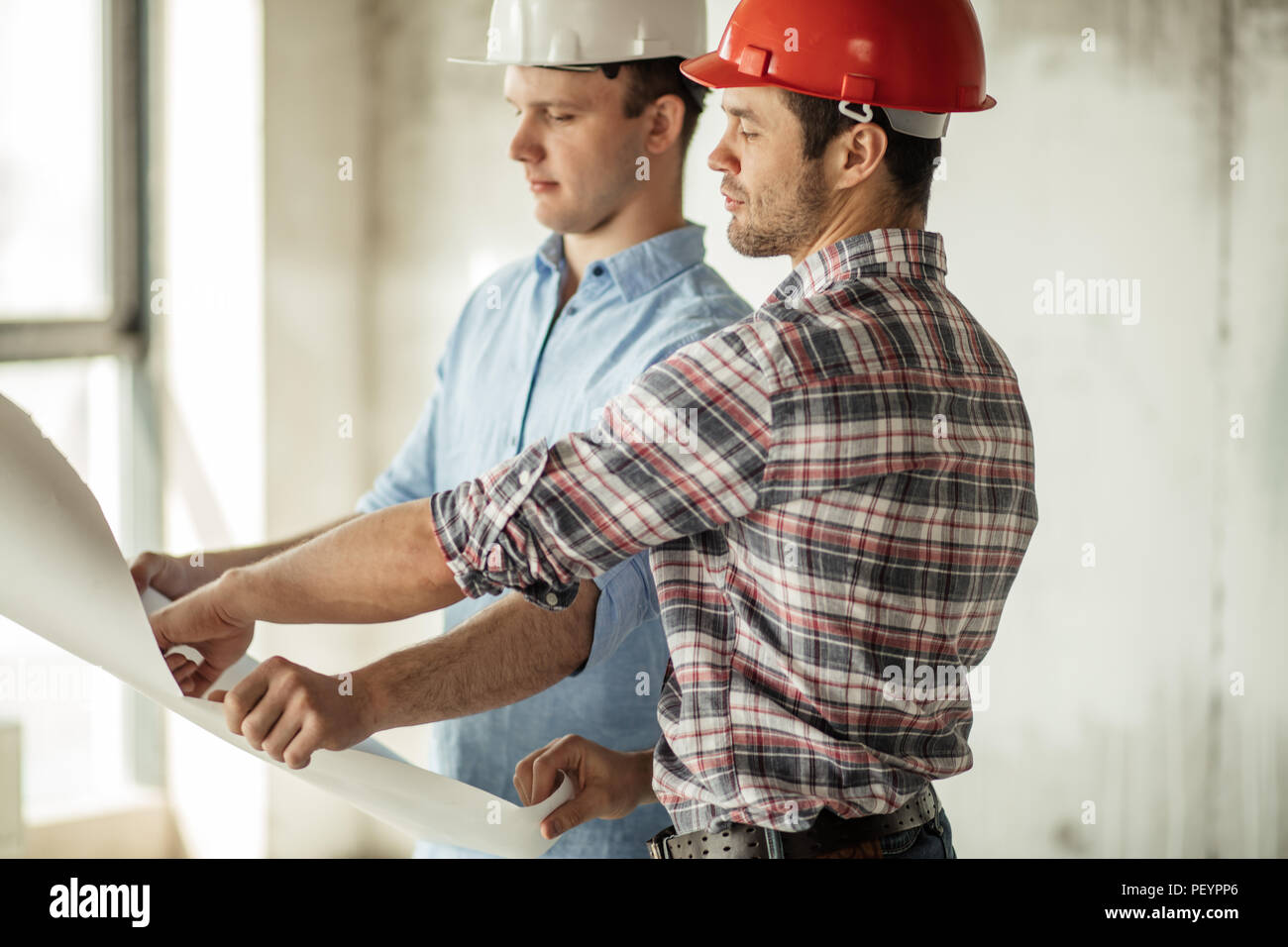 two engineers are making up the project at workplace.social service buildings - Stock Image