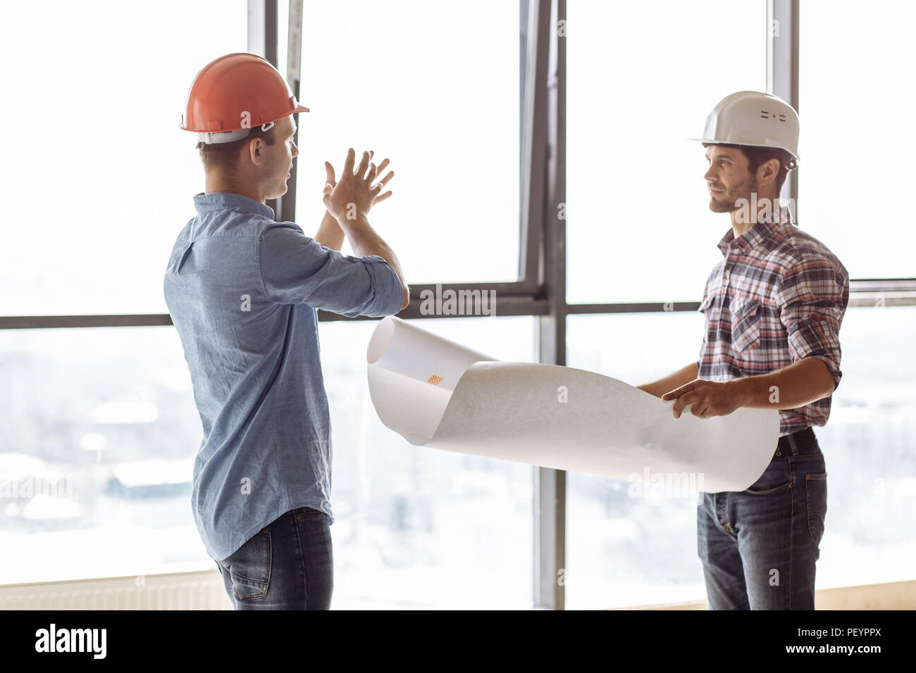 two ambitious hardworking architects are designing an extension.gesture concept. discussion at workplace - Stock Image