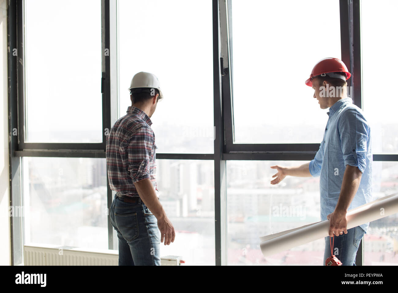 two builders are checking the new panorama windows in the office building - Stock Image