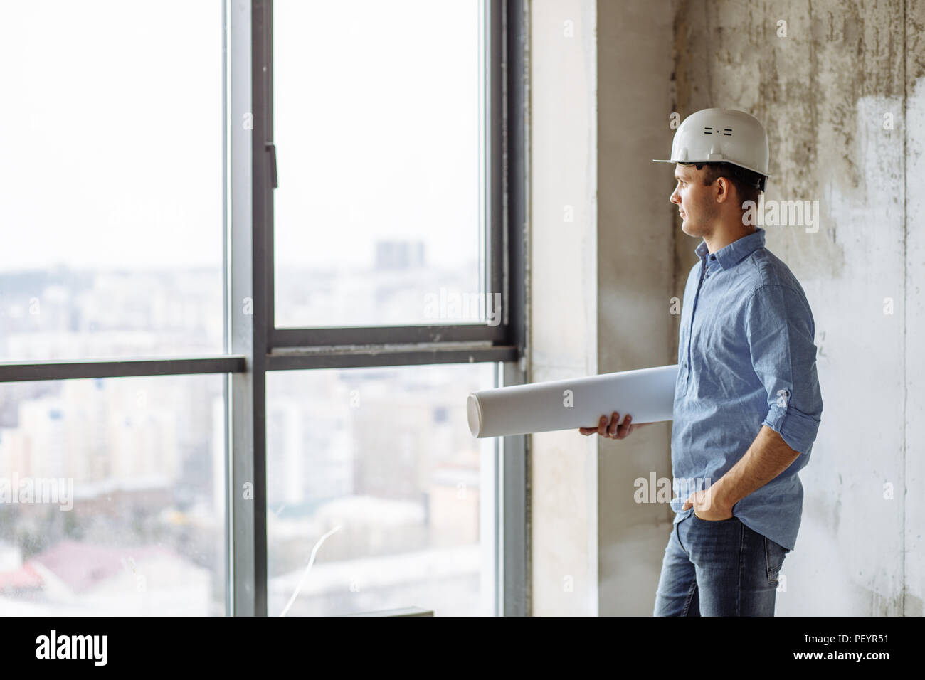 handsome guy in hardhat putting his hand on the pocket and looking at the panorama window. side view photo - Stock Image