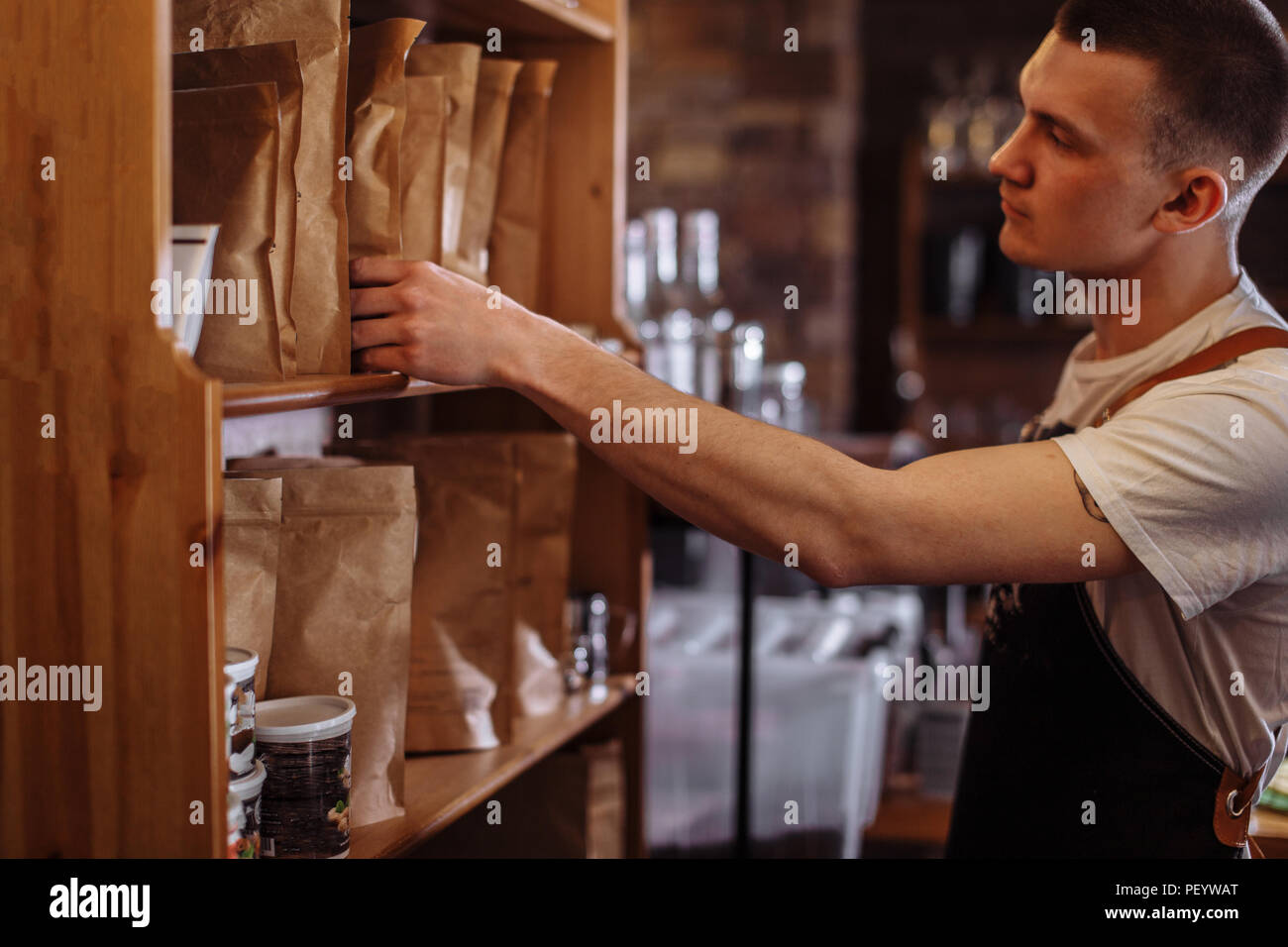 a handsome man is choosing the package with good coffee seeds - Stock Image