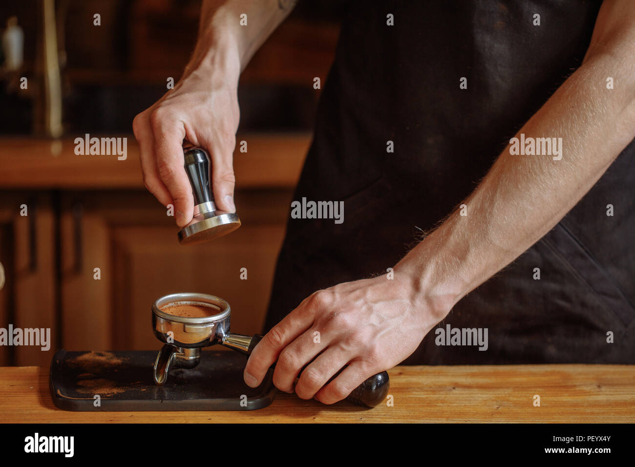 a barista is using a tamper to press coffee seads. close up cropped shot Stock Photo
