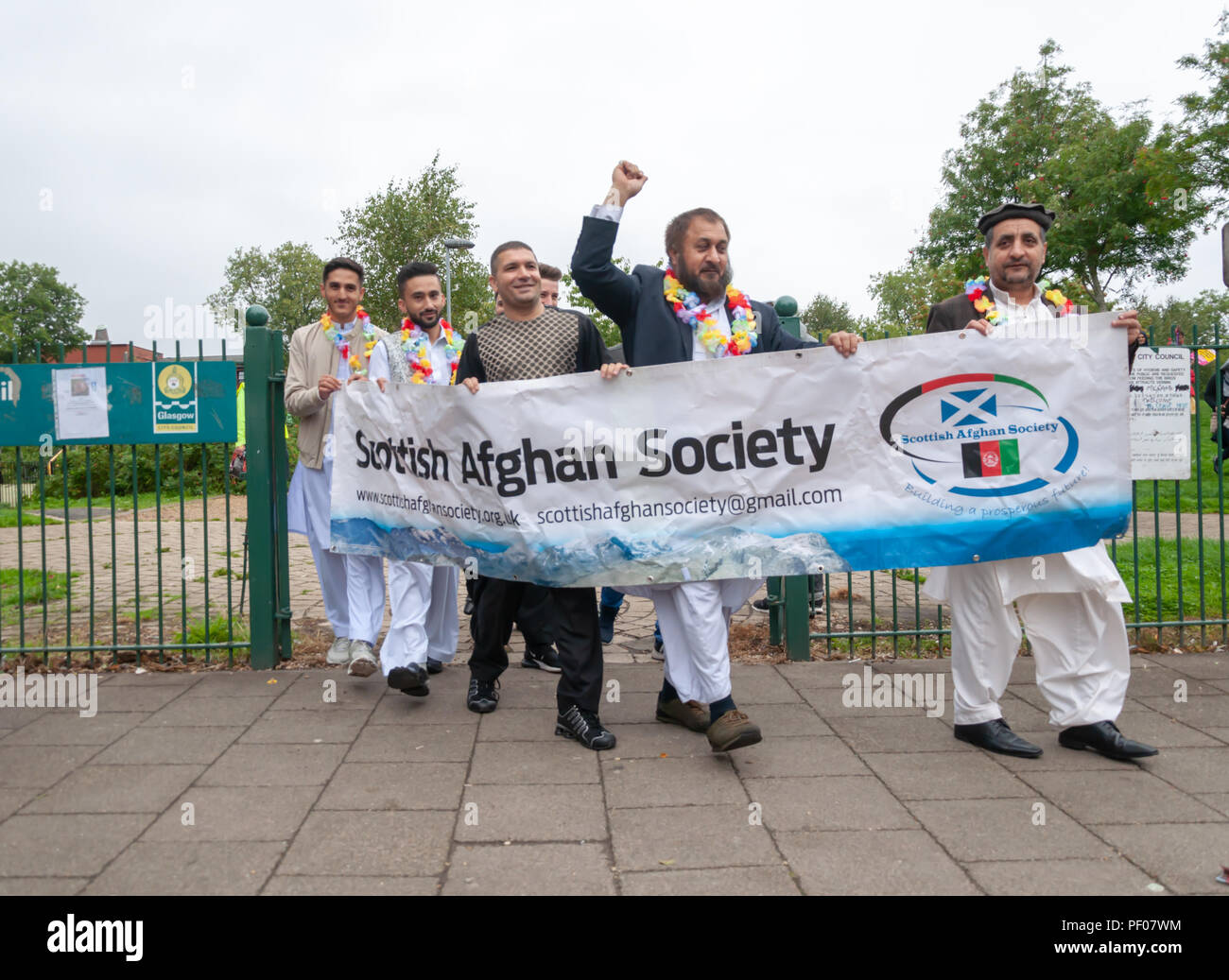 Glasgow, Scotland, UK. 18th August, 2018. A banner saying Scottish Afghan Society is carried at the start of the parade of the Govanhill International Festival & Carnival. This year's parade includes community groups, a pipe band, drummers, dancers, jugglers, roller skaters and a brass band all starting at Govanhill Park and travelling through the streets of Govanhill finishing at the Queen's Park Arena. Credit: Skully/Alamy Live News Stock Photo