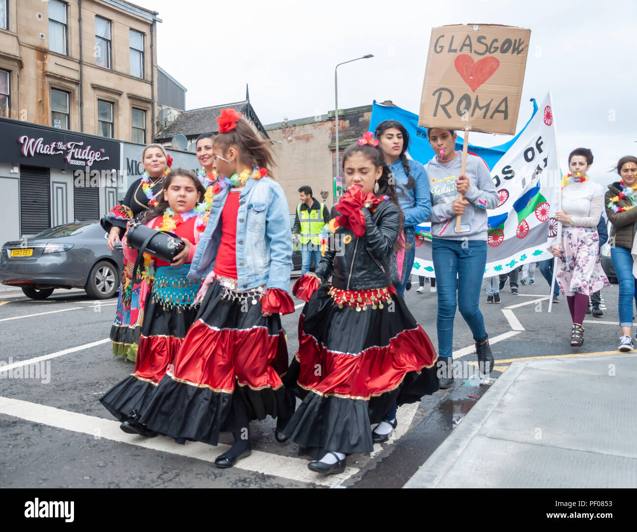 Glasgow, Scotland, UK. 18th August, 2018. Girls from the Roma Community in the parade of the Govanhill International Festival & Carnival. This year's parade includes community groups, a pipe band, drummers, dancers, jugglers, roller skaters and a brass band all starting at Govanhill Park and travelling through the streets of Govanhill finishing at the Queen's Park Arena. Credit: Skully/Alamy Live News - Stock Image