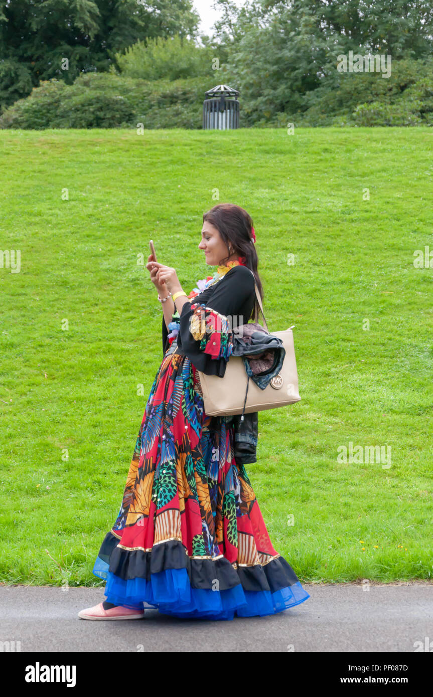 Glasgow, Scotland, UK. 18th August, 2018. A girl from the Roma Community takes a photo in the parade of the Govanhill International Festival & Carnival. This year's parade includes community groups, a pipe band, drummers, dancers, jugglers, roller skaters and a brass band all starting at Govanhill Park and travelling through the streets of Govanhill finishing at the Queen's Park Arena. Credit: Skully/Alamy Live News - Stock Image