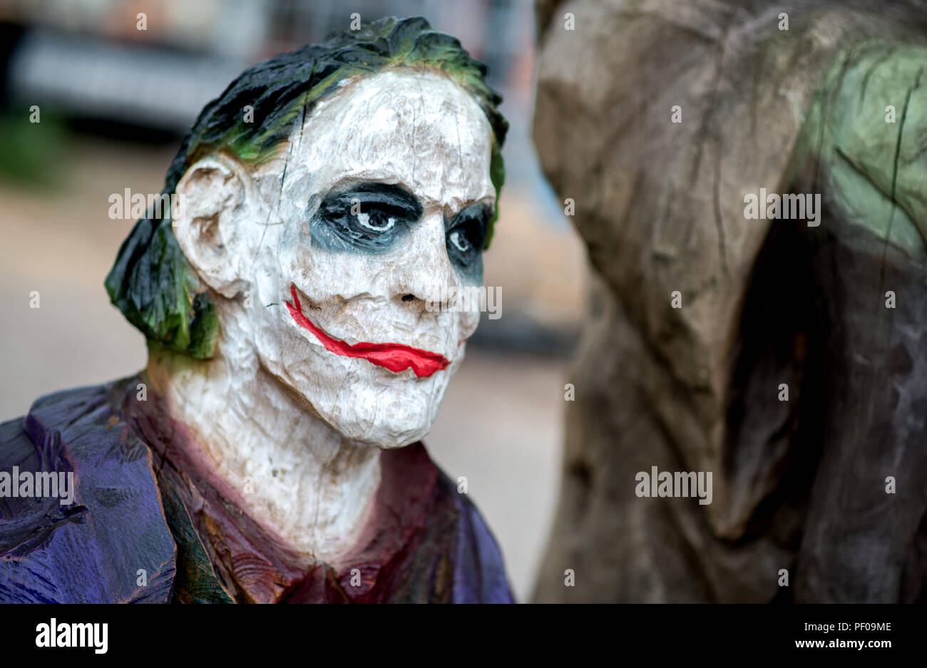 Saterland, Germany. 18th Aug, 2018. The wooden film character Joker stands on a pedestal during the Northwest German championship in chainsaw carving. A figure is carved out of wood with a chain saw during the discipline of speed carving. The wooden figures created in this way are auctioned off for a good cause. Credit: Hauke-Christian Dittrich/dpa/Alamy Live News - Stock Image