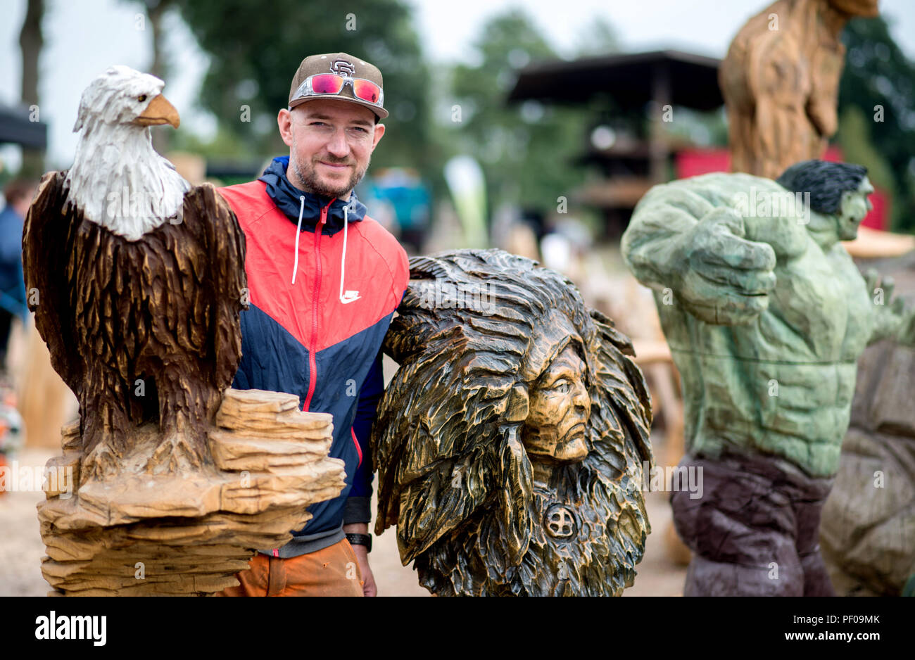 Saterland, Germany. 18th Aug, 2018. Wood artist and organizer Steffen Merla stands next to several wooden figures he made during the Northwest German Championship in chainsaw carving. A figure is carved out of wood with a chain saw during the discipline of speed carving. The wooden figures created in this way are auctioned off for a good cause. Credit: Hauke-Christian Dittrich/dpa/Alamy Live News - Stock Image