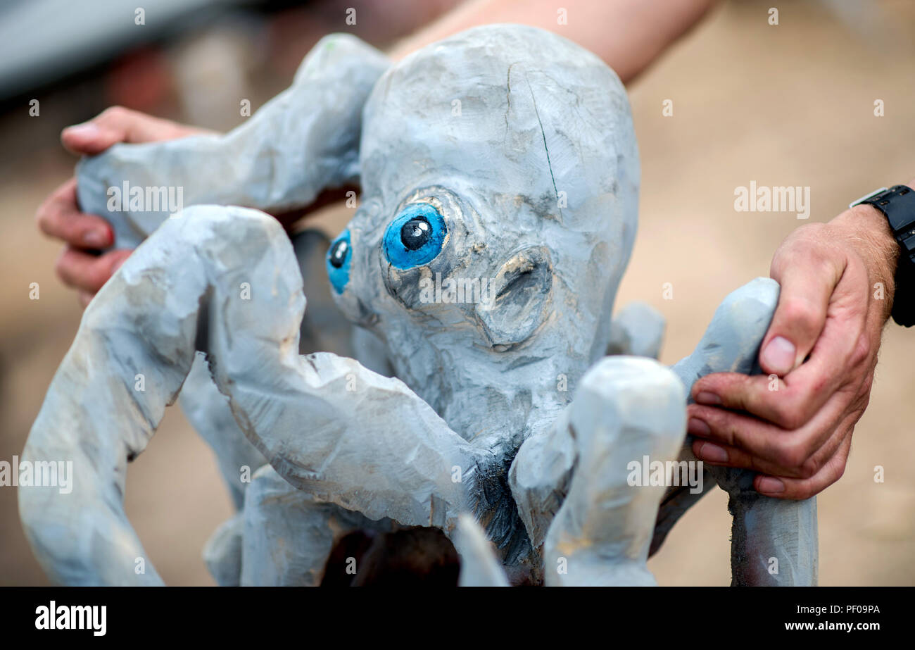 Saterland, Germany. 18th Aug, 2018. A wood artist puts a figure of an octopus made of wood on a pedestal during the Northwest German championship in chainsaw carving. A figure is quickly carved out of wood with a chain saw during the discipline of speed carving. The wooden figures created in this way are auctioned off for a good cause. Credit: Hauke-Christian Dittrich/dpa/Alamy Live News - Stock Image