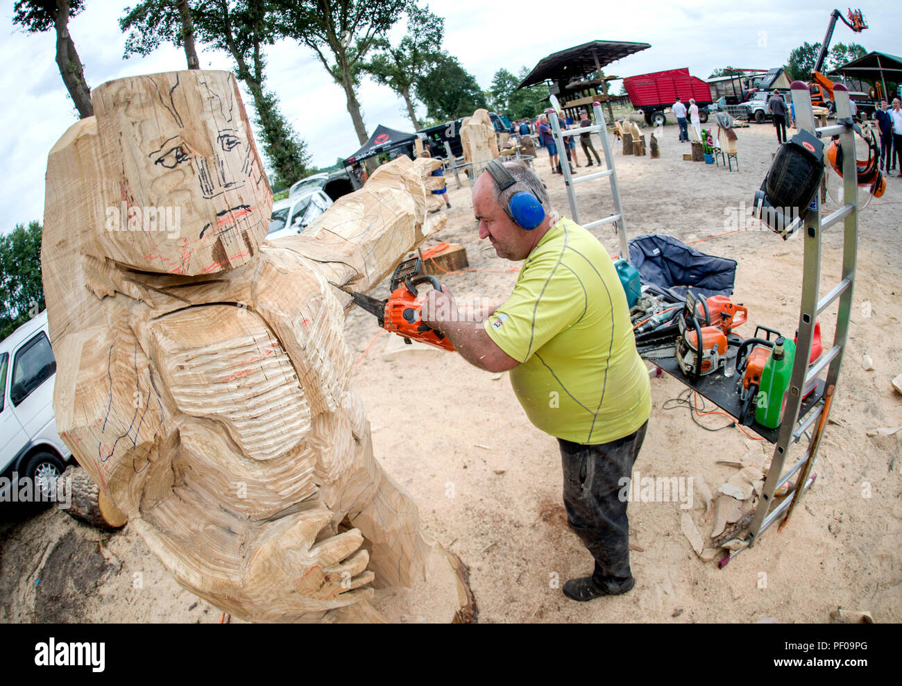 Saterland, Germany. 18th Aug, 2018. Wood artist Bernd Voigt from the Erzgebirge is working on a large wooden figure during the Northwest German championship in chainsaw carving. A figure is quickly carved out of wood with a chain saw during the discipline of speed carving. The wooden figures created in this way are auctioned off for a good cause. Credit: Hauke-Christian Dittrich/dpa/Alamy Live News - Stock Image