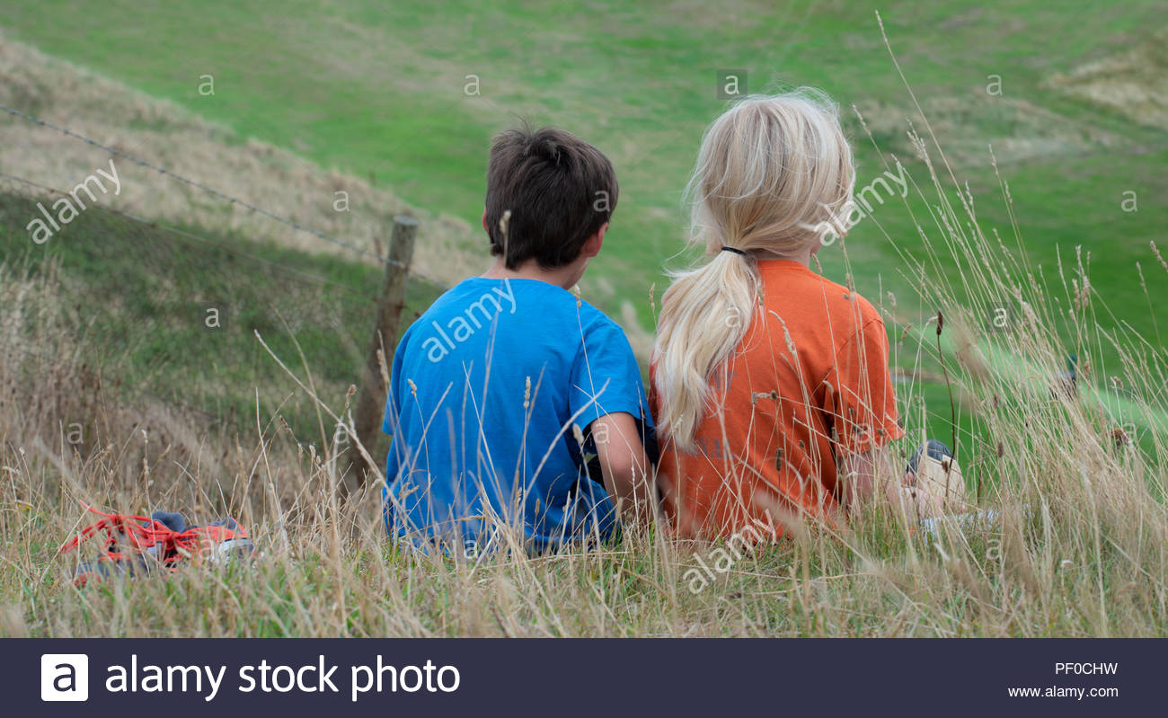 Burton Bradstock; Dorset, UK. 18th August 2018.  UK Weather: Cloudy and breezy, with warm spells at Burton Bradstock. Two children take a well earned rest following the steep climb from the beach on the South West Coast Path near Burton Bradstock ahead of Storm Ernesto.  Credit: PQ Images/Alamy Live News - Stock Image