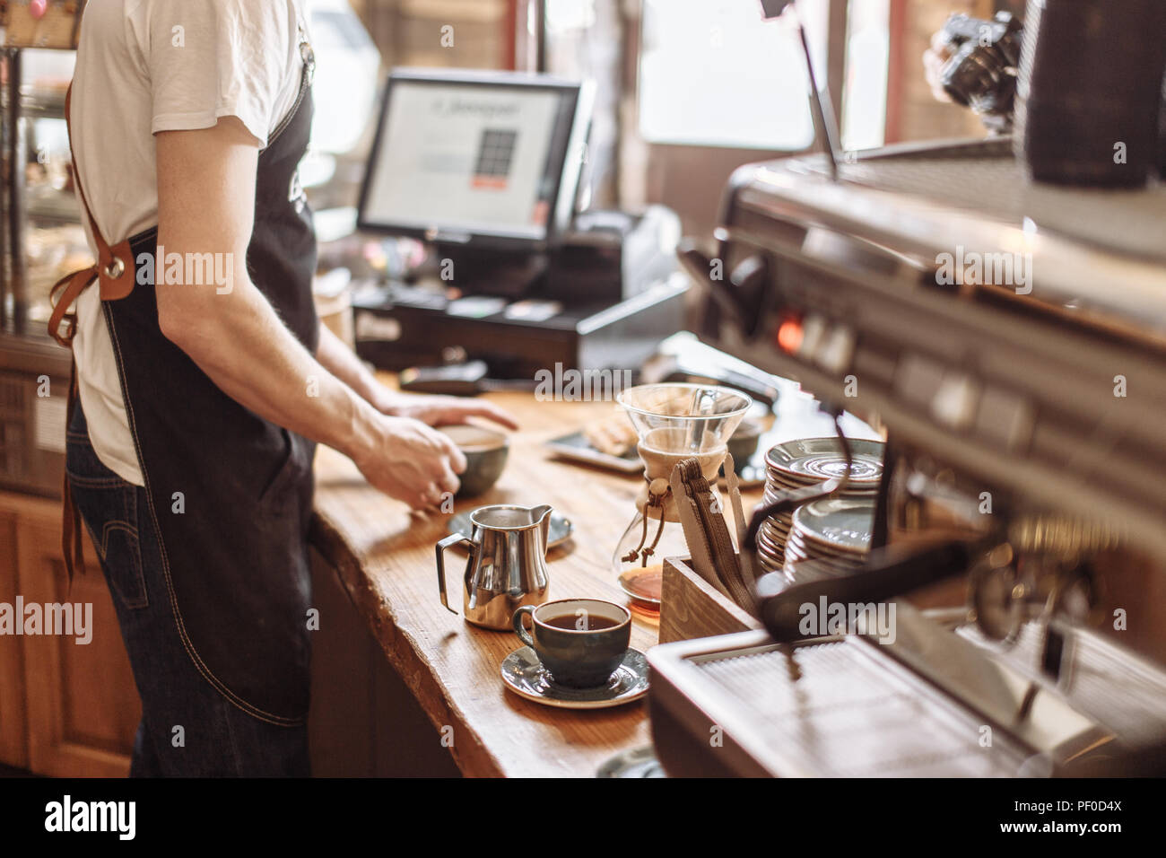 salesman is making espresso for clients in the coffee house - Stock Image