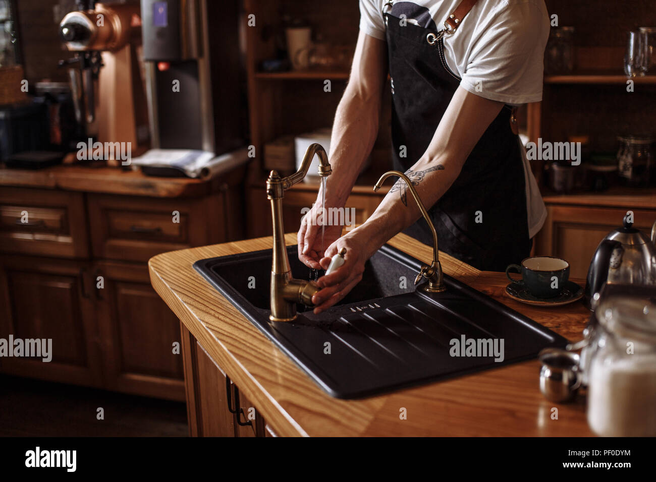 Portrait of young waiter washing his hands in kitchen at cafe. close up cropped photo - Stock Image