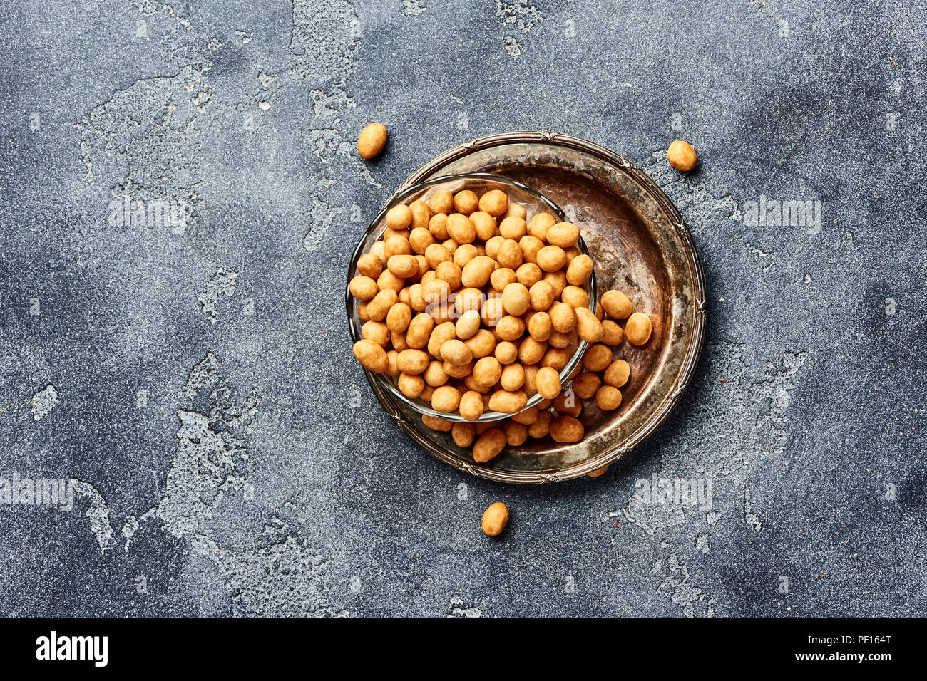 Spicy coated fried peanuts on gray background. Top view of snacks and nuts. - Stock Image
