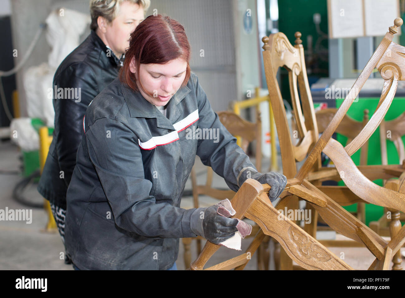 Belarus, the city of Gomel, on April 26, 2018. Furniture factory. The employee of the furniture department polishes the chair with a sandpaper. Furnit Stock Photo