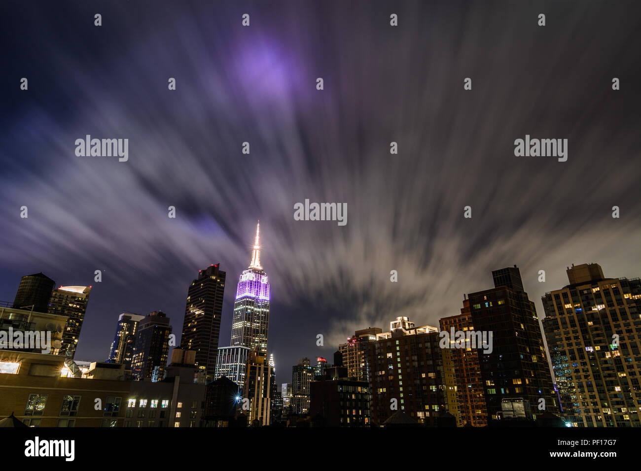 The Empire State Building lit up at night as fast moving clouds stream above the Chelsea neighborhood of New York City. - Stock Image